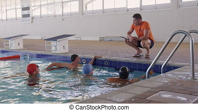 Front view of Caucasian male swimming coach and male swimmers at swimming pool, the couch crouching on the edge of the pool and talking to a group of swimmers, in slow motion
