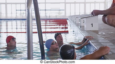 Swimming coach talking to swimmers - Side view of Caucasian ...