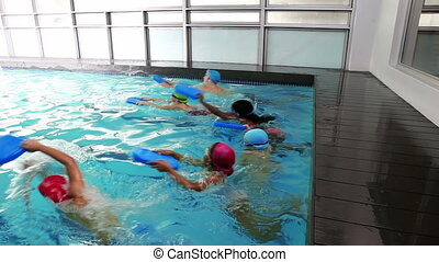 Swimming coach teaching children how to swim at the leisure...