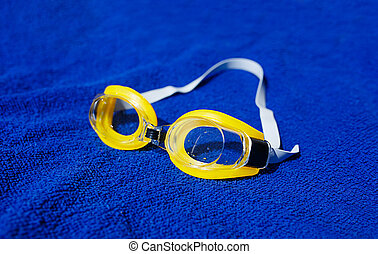 Swimming glasses at the towel. Shallow depth of field (dof).