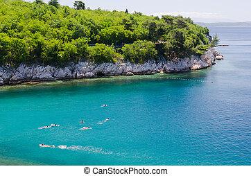 Swimming in green adriatic sea - group of teenagers swimming...