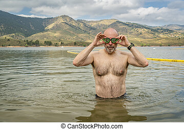active senior man finishing swimming workout in a mountain lake - Horsetooth Reservoir in northern Colorado