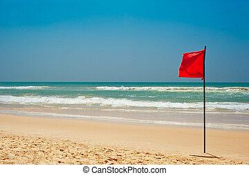 Swimming is dangerous in ocean waves. Red warning flag...