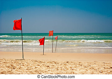 Swimming is dangerous in ocean waves. Red warning flag flapping in the wind on beach at stormy weather