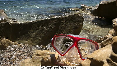 swimming mask laying on the shore washed by the waves