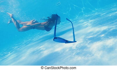 Swimming pool. A woman swims in the pool in sunglasses.