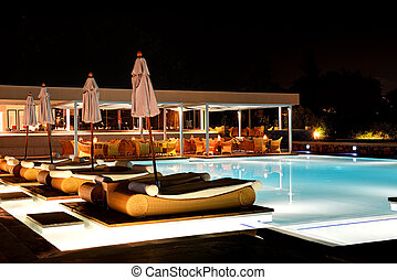 Swimming pool and bar in night illumination at the luxury hotel,