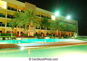 Swimming pool and building of the luxury hotel in night illumination, Fujairah, UAE