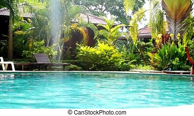 Swimming pool and palm trees in tropical garden with bamboo...