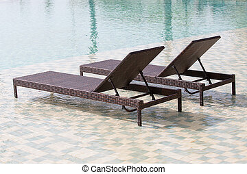 Swimming pool and two deck chairs, close up