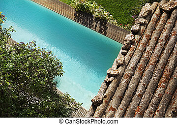 Swimming pool and weathered roof tiles in a garden