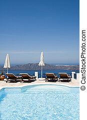 swimming pool at luxury resort overlooking the volcanic islands and caldera of famous santorini in the greek island town of imerovigli near oia