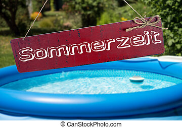 Summer time - Swimming pool in a garden and sign with the...