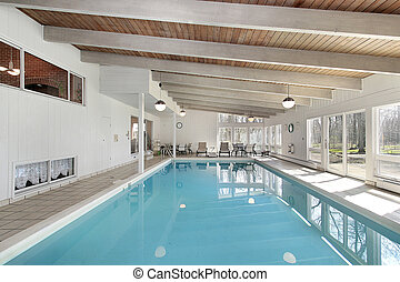 Swimming pool in luxury home with white beams
