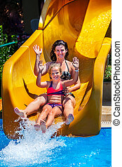 Swimming pool slides for family with children on water slide at aquapark .