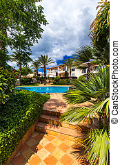Swimming pool, sun-loungers and palm trees during a warm sunny day, paradise destination for vacations. Backyard swimming pool with garden full of palm trees and flowers. Backyard with swimming pool.