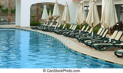Swimming pool with beach beds and sunshields - Swimming pool...