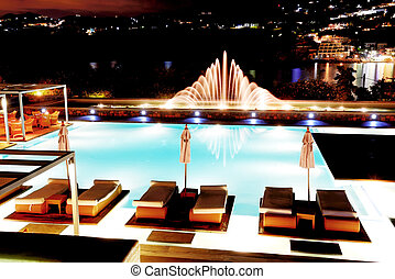 Swimming pool with fountain in night illumination at the luxury