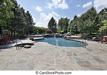 Swimming pool of luxury home with large stone patio