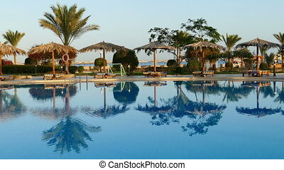 Swimming pool with palm trees in resort at morning