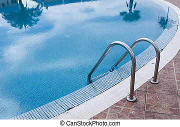 Swimming pool with stair at hotel near the beach close up