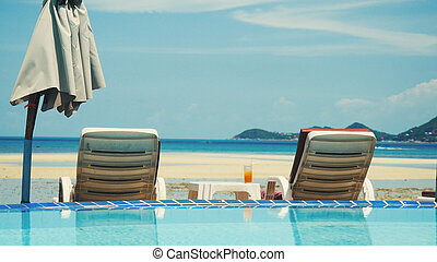 Swimming pool with sunbeds and cocktail near the sea on Koh Samui. Vacation concept.