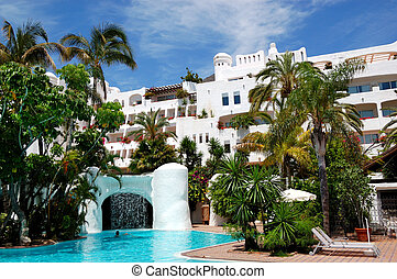 Swimming pool with waterfall and building of luxury hotel, Tenerife island, Spain