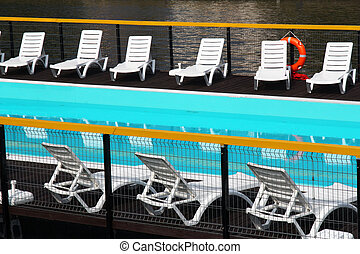 swimming pool with white chairs