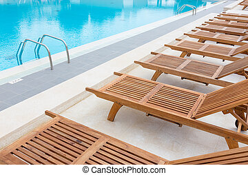 Swimming pool with wooden sunbeds.