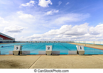 swimming start platform with number one two three and blue sky.