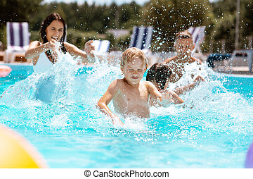Blonde son feeling amazing swimming with parents and sister