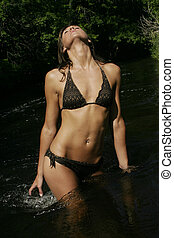 Swimsuit - Model in creative pose in middle of river.
