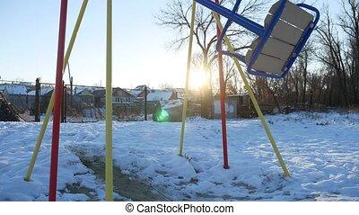 swing for children swinging on the playground snow sun glare winter
