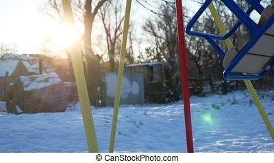 swing for children swinging on the playground snow winter sun glare