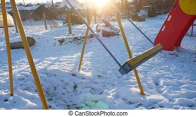 swing for children swinging sun glare on the playground snow winter
