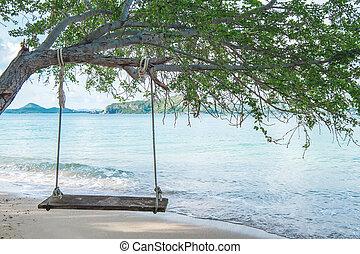 Swing hanging on tree on the beach
