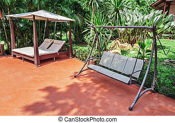 Swing on the patio in a tropical garden