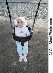 Swing - Cute little caucasian baby girl having fun on a...
