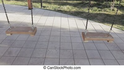 Swing swing on a chain - On the playground, a wooden swing...