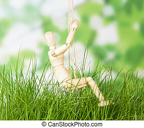 Swing with wooden dummy on abstract green background. -...