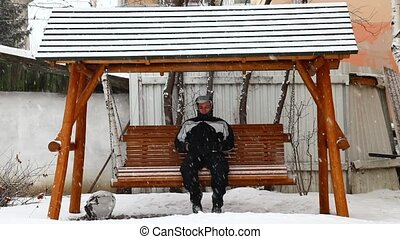 Swinging alone in wintertime - Man swinging alone in...