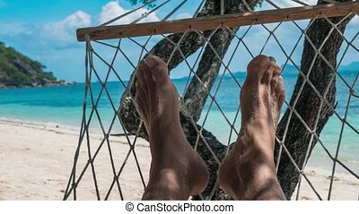 Swinging bare man feet in a hammock on vacation in front of the white sand beach and blue ocean