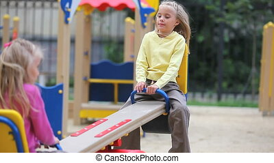 Swinging girls - Two cheerful little girls swinging in...