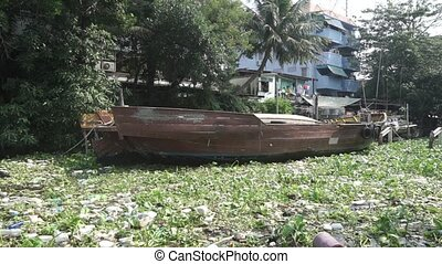 Swinging moored old boat in polluted water of Bangkok clip