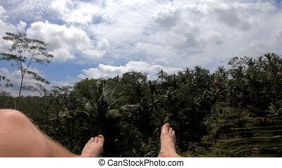 Tourist swinging high over Bali rice terrace