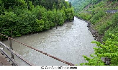 Swinging suspension bridge over a mountain river. Svaneti,...