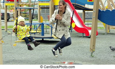 Swinging together - Mother and daughter swinging together on...
