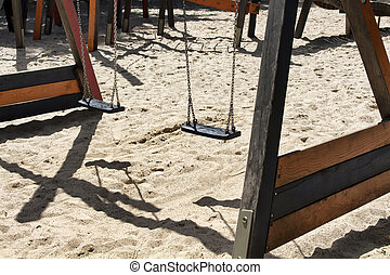Swings and their shadows at children playground at...