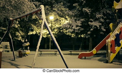 Swings Swaying In Empty Winter Park At Night