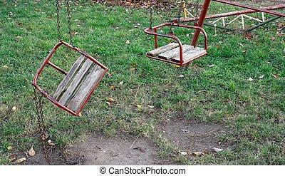 Swings - Two swings on a playground, one broken